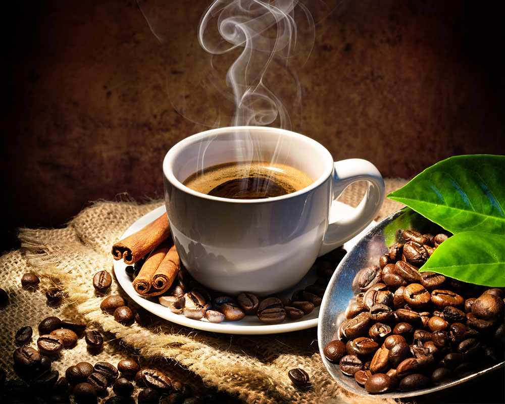 Coffee cup with steam and cinnamon surrounded by coffee beans